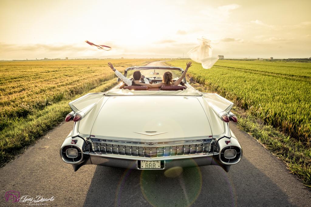 novios en Cadillac hacia el atardecer